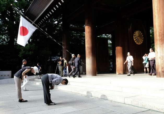 FILE - In this Aug. 15, 2013 file photo, worshippers bow at Yasukuni Shrine in Tokyo. Justin Bieber has apologized to those he offended by visiting Japan's Yasukuni war shrine the week of April 20, 2014, saying he was misled to see it as only a place of prayer. The Shinto shrine in Tokyo honors 2.5 million war dead, including 14 convicted war criminals. China and South Korea in particular see Yasukuni as a symbol of Japan's past militarism and see visits to it as a lack of understanding or remorse over wartime history. (AP Photo/Shizuo Kambayashi, File)  ORG XMIT: TOK102 Photo: Shizuo Kambayashi / AP