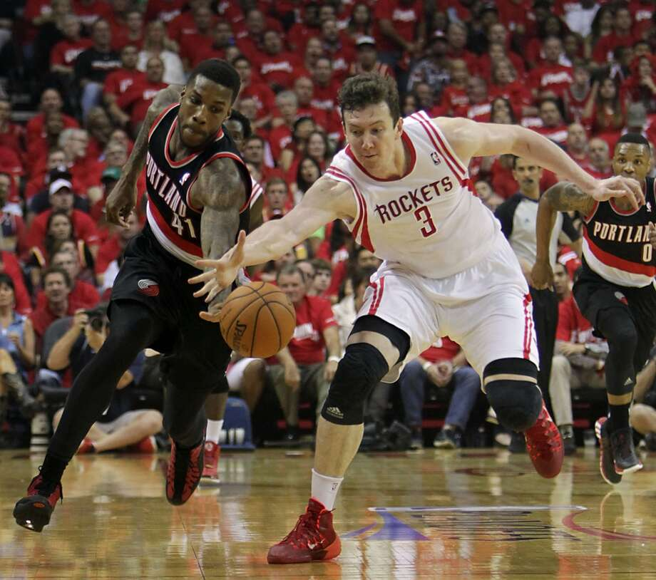 Trail Blazers forward Thomas Robinson left, and Rockets center Omer Asik right, chase a loose ball. Photo: James Nielsen, Houston Chronicle