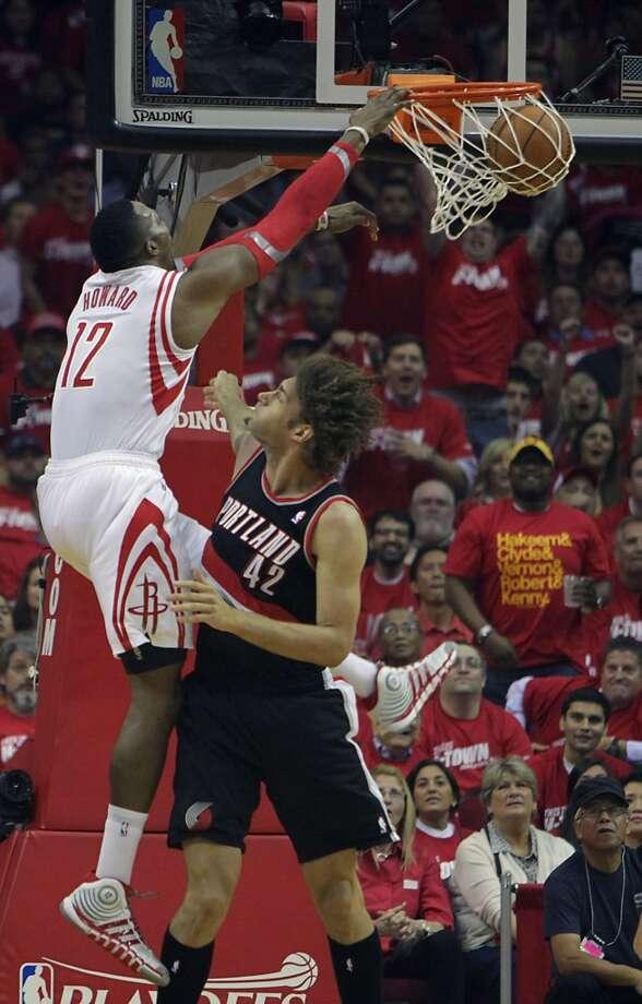 Rockets center Dwight Howard  left, dunks over Trail Blazers center Robin Lopez. Photo: James Nielsen, Houston Chronicle