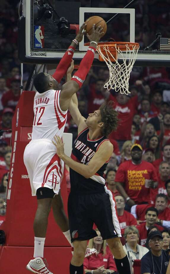 Rockets center Dwight Howard left, dunks over Trail Blazers center Robin Lopez. Photo: James Nielsen, Houston Chronicle