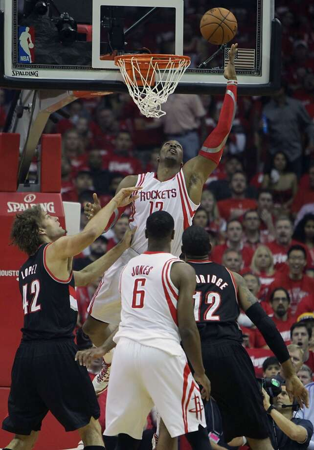 Rockets center Dwight Howard top, makes a basket as Trail Blazers center Robin Lopez left, and forward LaMarcus Aldridge right, look on. Photo: James Nielsen, Houston Chronicle