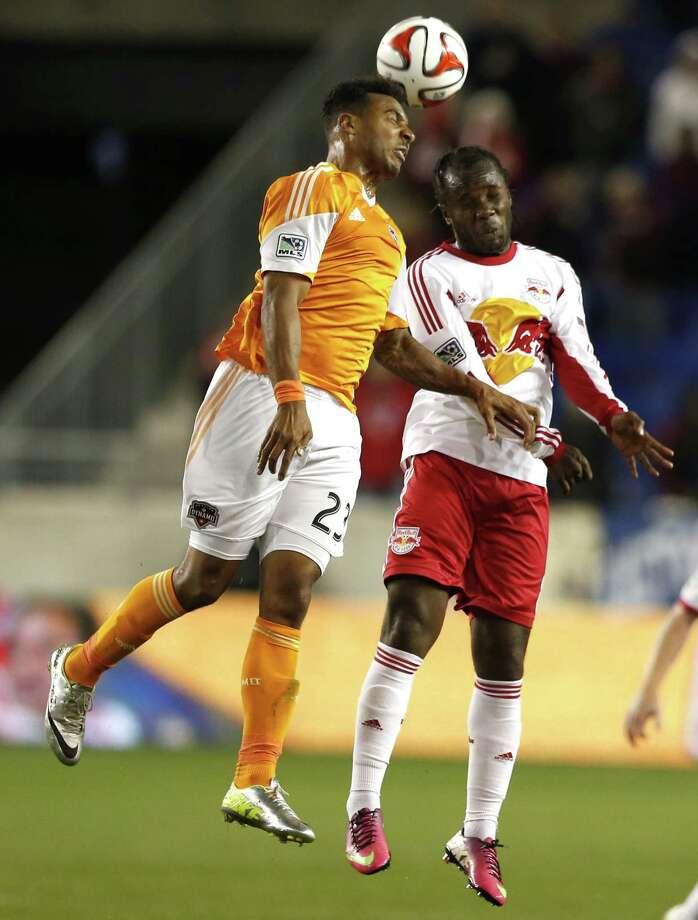 Houston Dynamo midfielder Giles Barnes, left, and New York Red Bulls forward Peguy Luyindula go up for the ball during the first half of an MLS soccer game on Wednesday, April 23, 2014, in Harrison, N.J. (AP Photo/Julio Cortez) Photo: Julio Cortez, Associated Press / AP