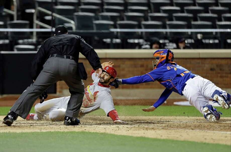 New York Mets catcher Travis d'Arnaud, right,tags out St. Louis Cardinals' Matt Carpenter (13) as home plate umpire Marty Foster watches the play during the ninth inning of a baseball game on Wednesday, April 23, 2014, in New York. The Mets won the game 3-2. (AP Photo/Frank Franklin II) ORG XMIT: NYM113 Photo: Frank Franklin II / AP