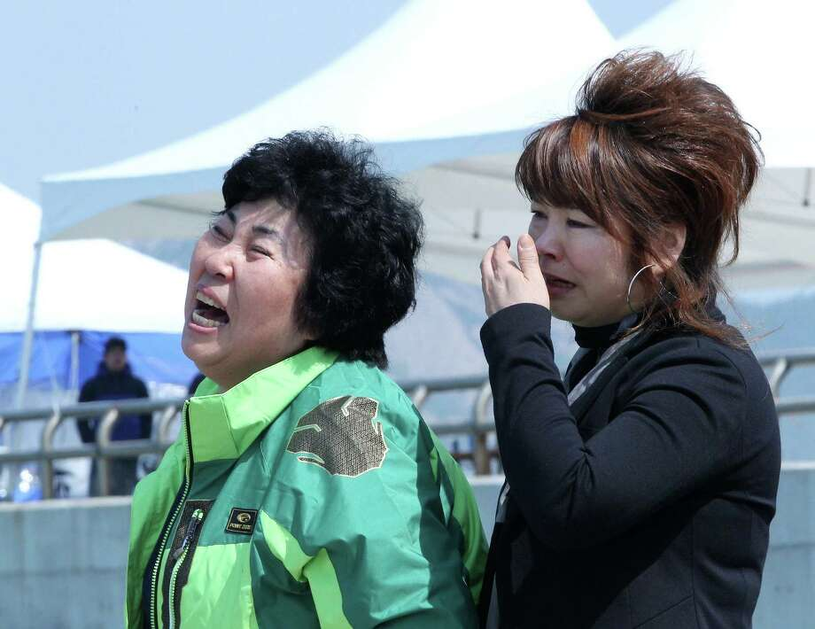 Relatives of a passenger aboard the sunken ferry weep as they wait for their missing loved one in Jindo, South Korea. More than 140 still are missing. Photo: Associated Press / AP