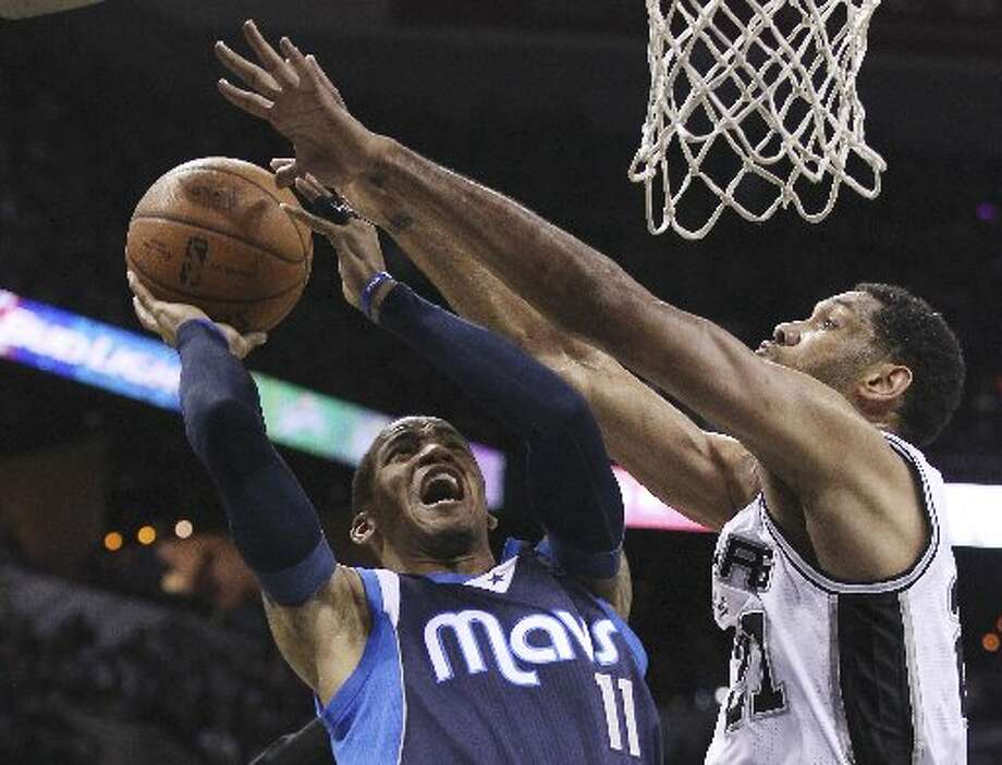 Spurs' Tim Duncan (21) tightly defends Dallas Mavericks' Monta Ellis (11) in the first half of Game 2 of the first round of the Western Conference playoffs at the AT&T Center on Wednesday, Apr. 23, 2014. (Kin Man Hui/San Antonio Express-News) Photo: Kin Man Hui/San Antonio Express-News