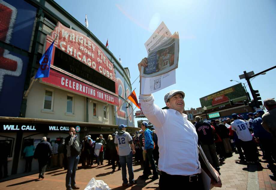 Apr 23, 2014; Chicago, IL, USA; Steve Gast hands out promotional copies of the Chicago Tribune before the baseball game between the Arizona Diamondbacks and Chicago Cubs at Wrigley Field. Today marks the 100th year anniversary of the stadium's opening. Mandatory Credit: Jerry Lai-USA TODAY Sports Photo: Jerry Lai, Reuters