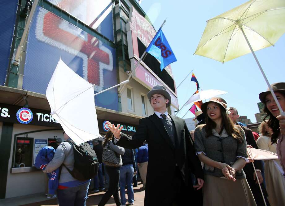 Apr 23, 2014; Chicago, IL, USA; Kyle Hadenfeld (left) of the Thodos Dance Chicago company performs by tossing an umbrella under the marquee before the baseball game between the Chicago Cubs and Arizona Diamondbacks at Wrigley Field. Today marks the 100th year anniversary of the stadium's opening. Mandatory Credit: Jerry Lai-USA TODAY Sports Photo: Jerry Lai, Reuters