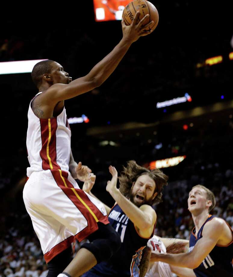 Miami Heat's Chris Bosh, left, shoots over Charlotte Bobcats' Josh McRoberts (11) during the first half in Game 2 of an opening-round NBA basketball playoff series, Wednesday, April 23, 2014, in Miami. (AP Photo/Lynne Sladky) ORG XMIT: AAA107 Photo: Lynne Sladky / AP