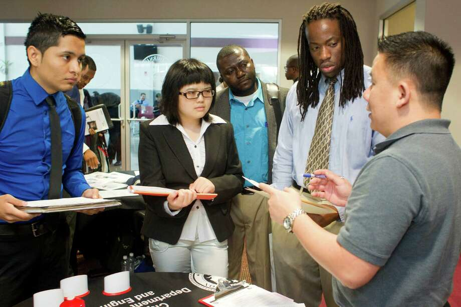 Bach Le, right, a human resources specialist with the city of Houston, talks with Texas Southern University students during a career fair this week. The U.S. class of 2014 has it better than students who graduated a year ago, college placement officers say. Photo: Johnny Hanson / © 2014  Houston Chronicle