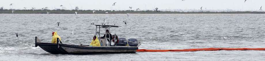 A boat stretches a containment boom in the Texas City ship channel in the aftermath of a March 26 oil spill. Photo: Kevin M. Cox / Associated Press / The Galveston County Daily News