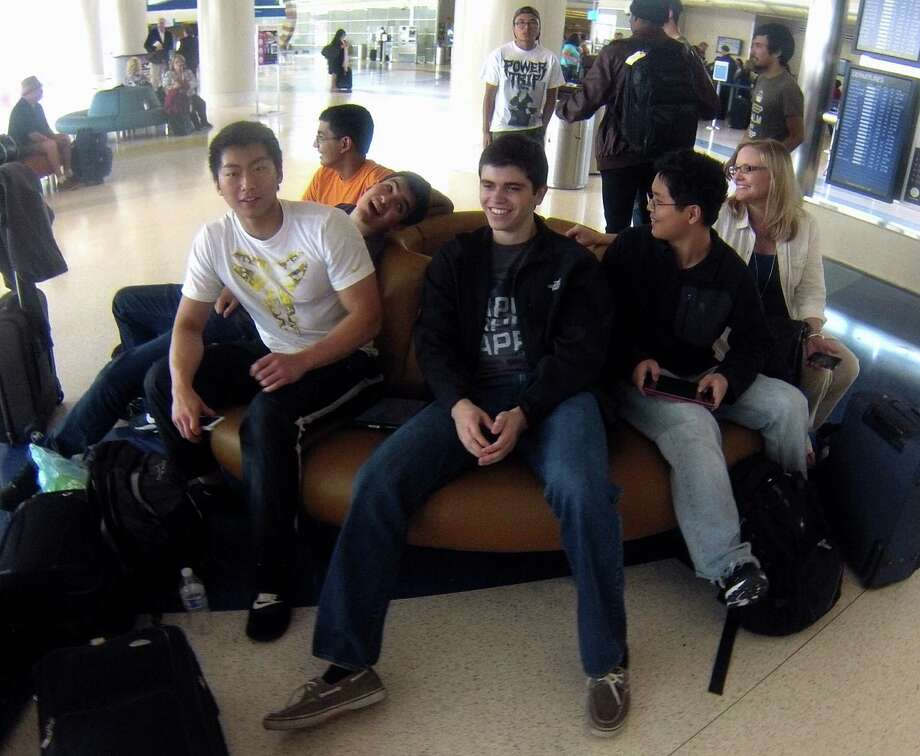 Brandeis High School students Frank Jing (from left), Pranjal Singh, Christian Castellanos, Charles Kennedy and Stephen Chen and their teacher, LeAnne Gisler, wait to board a flight to Washington, D.C., to compete in the National Science Bowl. Photo: Billy Calzada / San Antonio Express-News / San Antonio Express-News