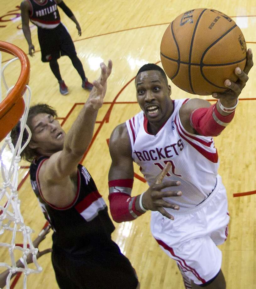 Houston Rockets center Dwight Howard (12) drives past Portland Trail Blazers center Robin Lopez for a layup during the first half of Game 2 of the NBA Western Conference Quarterfinals at Toyota Center Wednesday, April 23, 2014, in Houston. ( Brett Coomer / Houston Chronicle ) Photo: Brett Coomer, Houston Chronicle