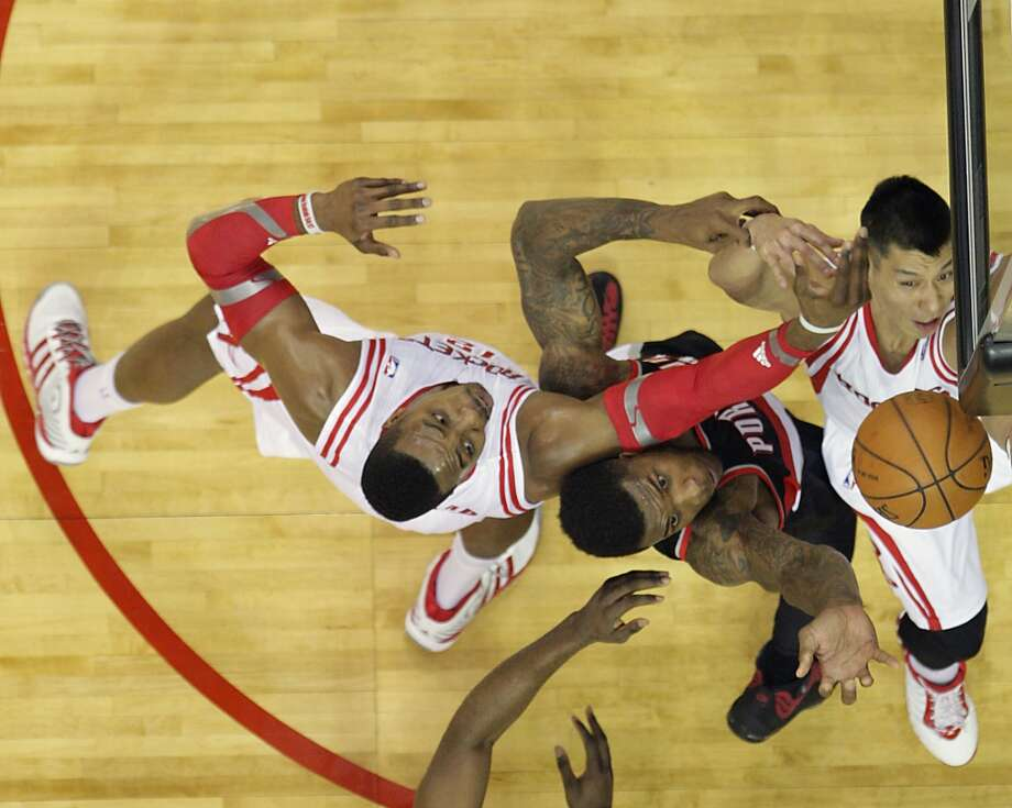 Houston Rockets center Dwight Howard left, Portland Trail Blazers forward Thomas Robinson center and Houston Rockets guard Jeremy Lin right, jump for a rebound during the first half of game two of the Western Conference Quarterfinals playoffs at the Toyota Center Wednesday, April 23, 2014, in Houston. ( James Nielsen / Houston Chronicle ) Photo: James Nielsen, Houston Chronicle