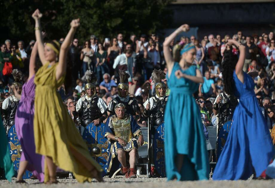 A man dressed as Nero, above, watches women dance at Circus Maximus;. Photo: Filippo Monteforte, AFP/Getty Images