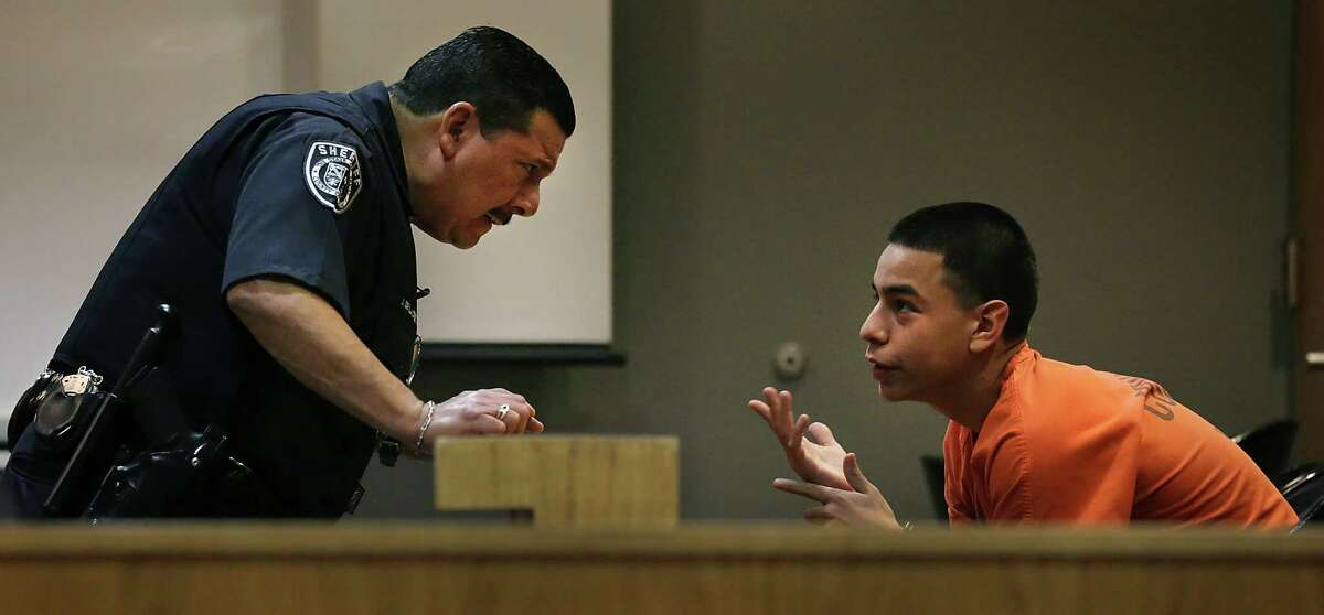 John Gonzales III, right, a juvenile who was certified to stand trial as an adult, talks with Bexar County Sheriff Deputy De La Cruz, as he waits to be sentence by Judge Laura Parker in the 386th District Court. Gonzales was sentenced to the maximum 20 years, on murder charges related to the murder of James Whitley, in Aug. of 2012. Wednesday, April 23, 2014.