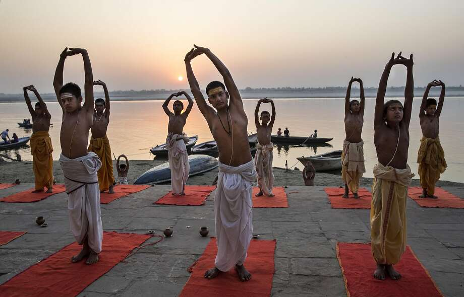 VARANASI, INDIA - APRIL 23:  Young Indian Hindu Brahmins training to be priests perform yoga on a ghat on the Ganges River, holy to Hindus, at sunrise on April 23, 2014 in Varanasi, India.  (Photo by Kevin Frayer/Getty Images) *** BESTPIX *** Photo: Kevin Frayer, Getty Images