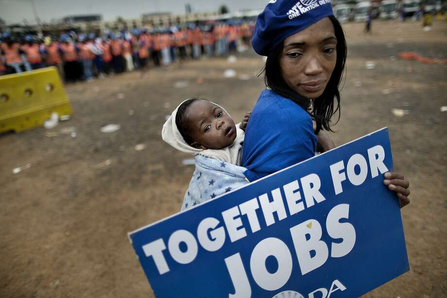 TOPSHOTS A supporter of the Democratic Alliance, South Africa's main opposition party, holds a placard while carrying her baby as she marches towards the office of the Gauteng province premier in Johannesburg on April 23, 2014 during a protest against corruption and unemployment. South Africa is due to hold general elections on May 7. AFP PHOTO / MARCO LONGARIMARCO LONGARI/AFP/Getty Images Photo: Marco Longari, AFP/Getty Images