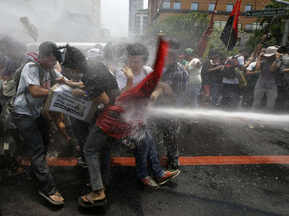 Police train their fire hose at protesters as the latter try to force their way closer to the U.S. Embassy for a rally against next week's visit of U.S. President Barack Obama, in Manila, Philippines, Wednesday, April 23, 2014. Philippine police armed with truncheon, shields and water hose have clashed with more than 100 left-wing activists who rallied at the U.S. Embassy in Manila to oppose a visit by Obama and a looming pact that will increase the American military presence in the Philippines. (AP Photo/Bullit Marquez) Photo: Bullit Marquez, Associated Press