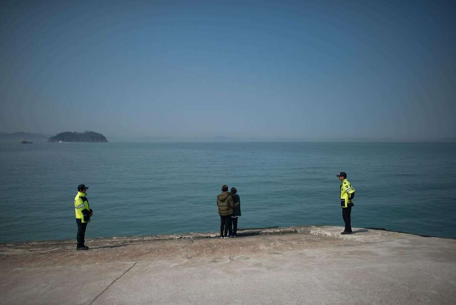 TOPSHOTS Relatives (C) of missing passengers of the 'Sewol' ferry stand before the sea at Jindo harbour on April 23, 2014. The confirmed death toll from South Korea's ferry disaster crossed 100 on April 22, as dive teams, under growing pressure from bereaved relatives, accelerated the grim task of recovering hundreds more bodies from the submerged vessel.  AFP PHOTO / ED JONESED JONES/AFP/Getty Images Photo: Ed Jones, AFP/Getty Images