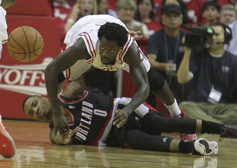 Rockets guard Patrick Beverley dives over Trail Blazers guard Damian Lillard while chasing a loose ball. Photo: James Nielsen, Houston Chronicle