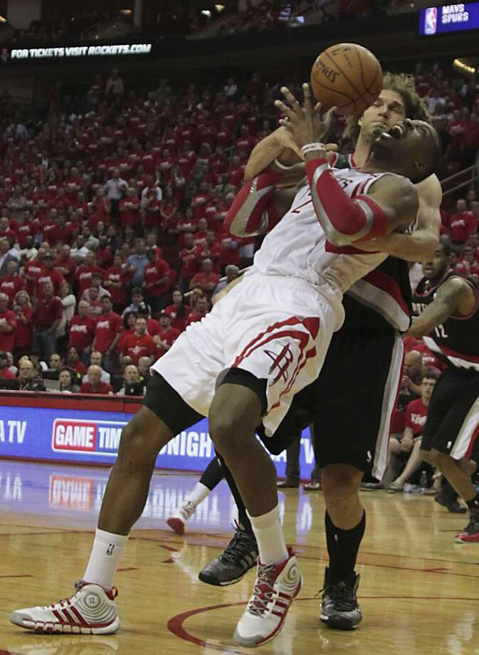 Rockets center Dwight Howard is fouled by Trail Blazers center Robin Lopez. Photo: James Nielsen, Houston Chronicle