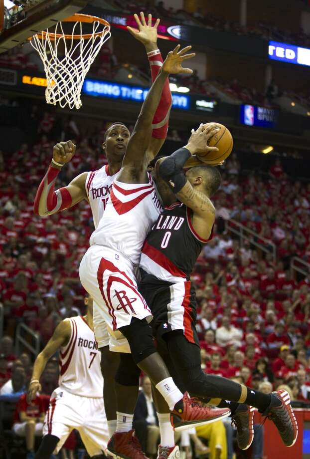Trail Blazers guard Damian Lillard (0) drives to the basket and is fouled by Rockets guard Patrick Beverley. Photo: Brett Coomer, Houston Chronicle