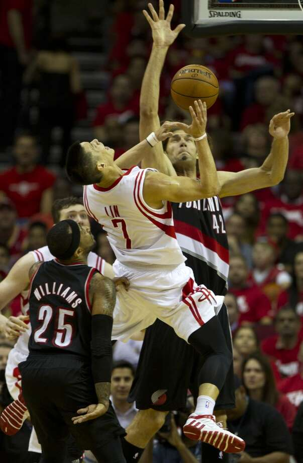 Rockets guard Jeremy Lin (7) is fouled by Trail Blazers center Robin Lopez (42) as he drives to the basket. Photo: Brett Coomer, Houston Chronicle