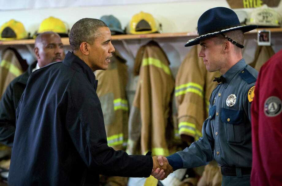 President Barack Obama shakes hands with Washington State Patrol Trooper Rocky Oliphant. The trooper was one of the first rescuers on the scene of the mudslide. Photo: JOSHUA TRUJILLO, SEATTLEPI.COM / SEATTLEPI.COM