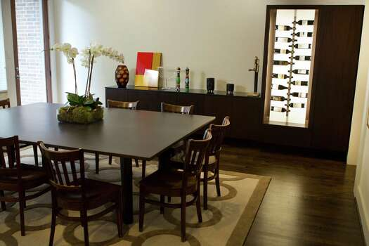 Ziggy Gruber designed the illuminated wine cabinet and display case in his dining room.  Photo: Brett Coomer, Staff / © 2014 Houston Chronicle