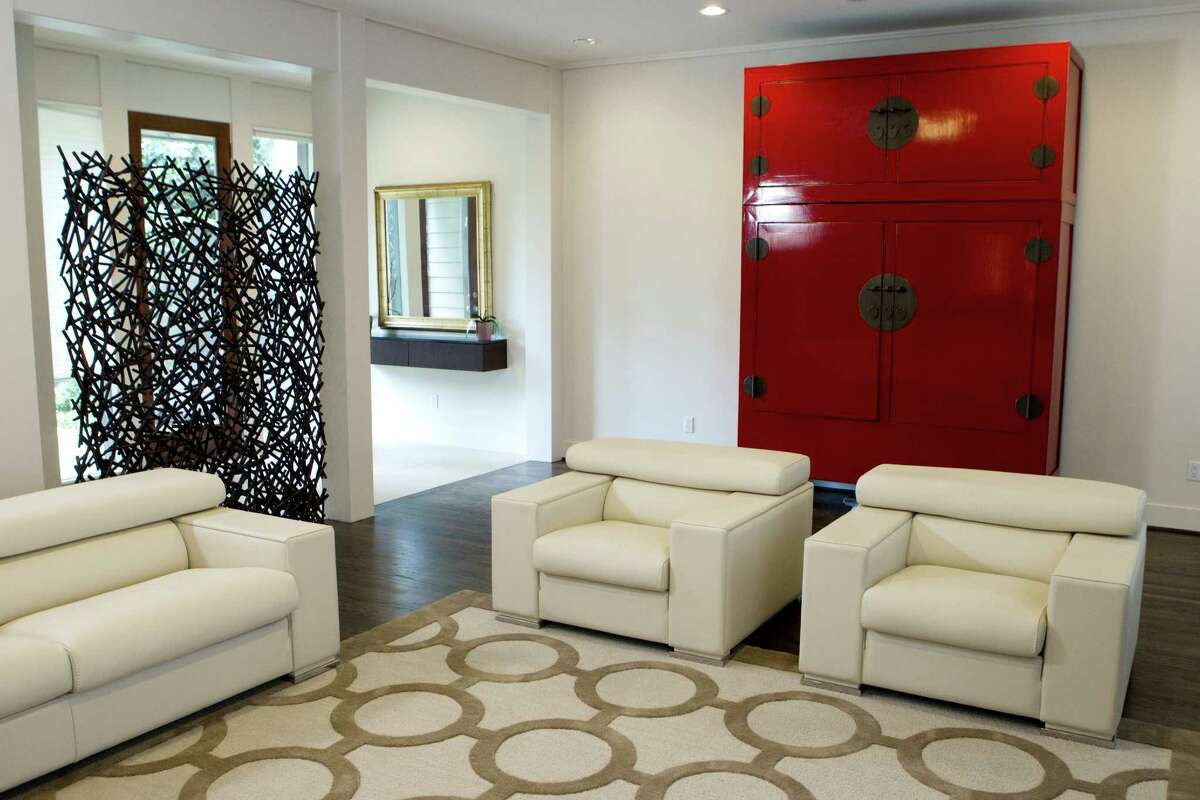 Near the entranceway, contemporary neutral seating and a red lacquered antique Chinese cabinet mark the living room. ( Brett Coomer / Houston Chronicle )
