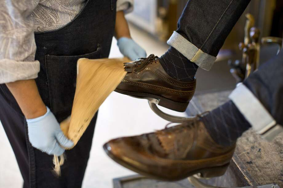 Vasti Porter, the master bootblack at Wingtip, gives a guest a shoe shine during the Style Launch event at Wingtip a to celebrate the San Francisco Chronicle's newly reimagined Style section at the store in San Francisco, Calif., on Wednesday, April 23, 2014. Photo: Laura Morton, Special To The Chronicle