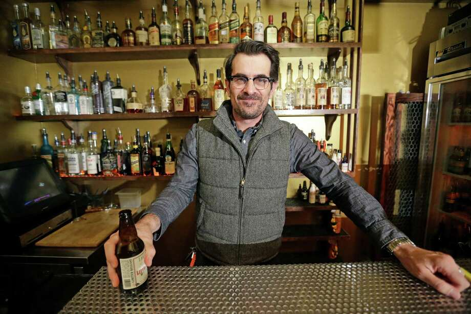 "In this April 16, 2014 photo, actor Ty Burrell, who plays bumbling dad Phil Dunphy on ABC's ""Modern Family,"" poses holding a beer at Bar X, the cocktail bar he co-owns, in Salt Lake City. Burrell just opened Beer Bar, a beer garden-like eatery next door to Bar X that serves 150 beers paired up with an array of house-made bratwursts, local breads and Belgian fries. The restaurant sports long tables and benches with high ceilings to evoke that Bavarian beer hall feel. (AP Photo/Rick Bowmer) Photo: Rick Bowmer, STF / AP"
