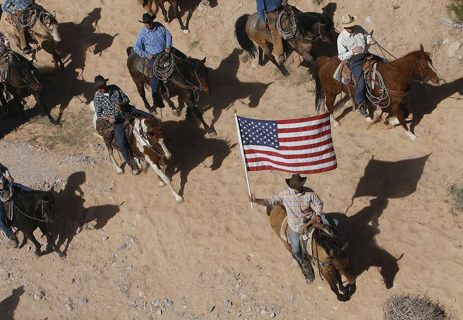 FILE - In this April 12, 2014, file photo, the Bundy family and their supporters fly the American flag as their cattle is released by the Bureau of Land Management back onto public land outside of Bunkerville, Nev.  The federal Bureau of Land Management says six cattle died in the roundup of animals it says rancher Cliven Bundy allowed to graze illegally on public land outside his southern Nevada property. The BLM said Tuesday, April 22, 2014, that two of four animals that were euthanized bore Bundy brands. (AP Photo/Las Vegas Review-Journal, Jason Bean, File) LOCAL TV OUT; LOCAL INTERNET OUT; LAS VEGAS SUN OUT Photo: Jason Bean, Associated Press