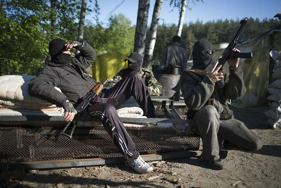 Pro-Russian armed men rest as they guard a checkpoint near Krasny Linam village outside Slovyansk, Ukraine, Thursday, April 24, 2014. Ukrainian forces on Thursday killed at least two pro-Russian insurgents in the country's tumultuous east, an escalation that prompted Russian President Vladimir Putin to threaten unspecified consequences. (AP Photo/Alexander Zemlianichenko) Photo: Alexander Zemlianichenko, Associated Press