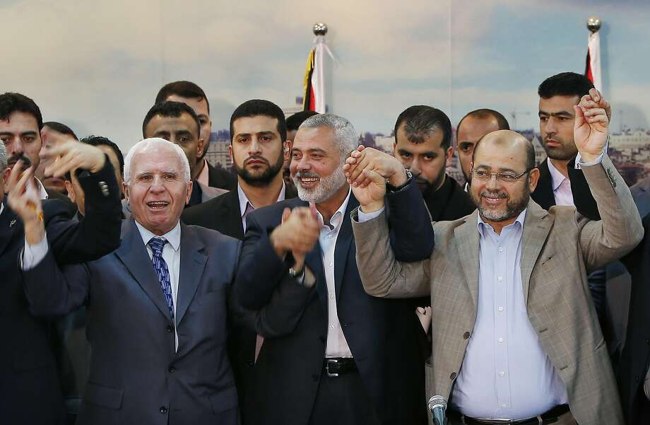 Fatah and Hamas officials celebrate after announcing a reconciliation accord in Gaza City. Photo: Suhaib Salem, Reuters