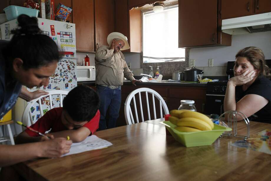 "Both unemployed, Jose Pineda Rivas, 61, center, stands in the kitchen with his wife, Maria Callejas, 43, right, as Ruth Fuentes, 32, left, helps her son Jose, 6, with his homework at Fuentes' home April 10, 2014 in Mendota, Calif. Rivas and his wife have been living with the Fuentes' family for four years. Rivas came to the United States in 1988 and was joined by his wife 3 years ago. They left five children behind in El Salvador, who they send money to every month. Both Rivas and his wife work in the fields for their income. Right now neither of them have been able to find steady work and the stress is taking its toll. Rivas has been having trouble sleeping and eating due to a constantly upset stomach and a toothache he cannot afford to repair. ""Our biggest worry is that tomorrow there is not going to be a job,"" said Rivas in Spanish through a translator. The historic drought combined with zero percent water allocation for farmers in the San Joaquin Valley means that many farmers are fallowing fields and many field workers are unemployed. In Mendota, a rural city of about 11,000 people about 35 miles west of Fresno, the jobless rate is 36 percent. Mayor Robert Silva is concerned that this summer it may reach as high as 50 percent. Though there are still precious few jobs this year in the fields, the streets of Mendota, which are usually empty in the middle of the day, are now haunted by people drifting up and down 7th Street, looking for work. Others families have already left to find work elsewhere. The schools have noticed a drop in attendance due to migration, 33 students have left with their families so far this year. Photo: Leah Millis, San Francisco Chronicle"