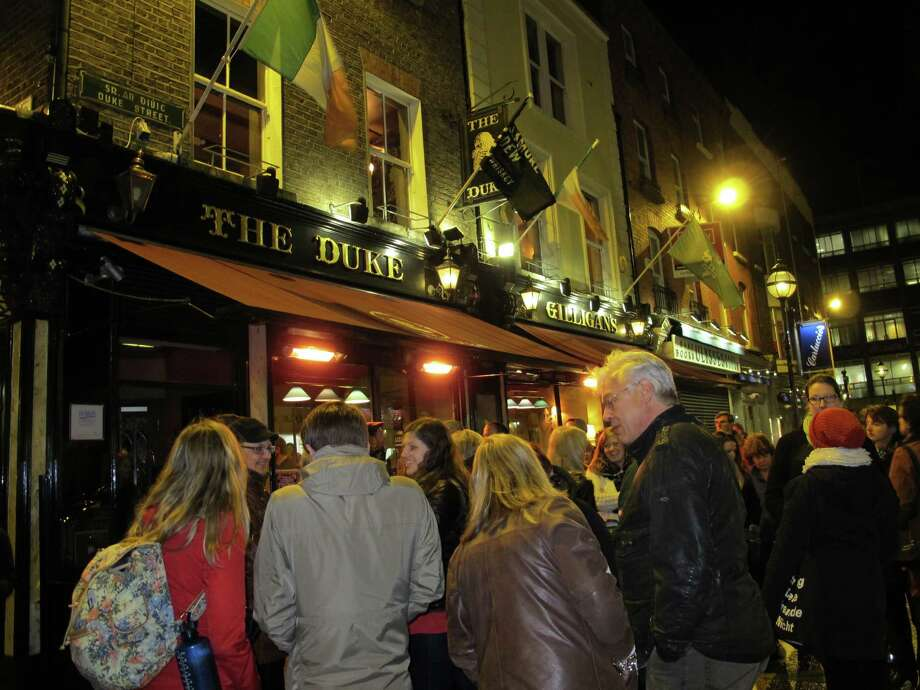 This March 20, 2014 photo shows a group of people gathered outside The Duke pub in Duke Street in Dublin, Ireland at the start of a literary pub crawl. Dublin is famous for its writers and wits and many of the city's 1,000 or so pubs were featured in their works. The literary tour takes visitors to several as actors re-enact scenes from the works of James Joyce, Brendan Behan, Oscar Wilde and others. (AP Photo/Helen O'Neill)  ORG XMIT: MER2014042112375766 Photo: Helen O'Neill / AP