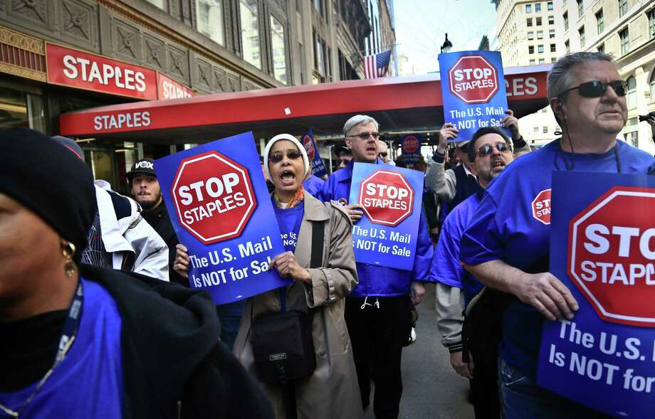 "Post office workers march outside a Staples store chanting ""Stop Staples, the U.S. mail is not for sale,"" Thursday April 24, 2014 in New York.  Thousands of postal workers around the nation are expected to picket outside Staples' stores to protest a pilot program of postal counters in the stores that are staffed with Staples employees.  (AP Photo/Bebeto Matthews) ORG XMIT: NYBM103 Photo: Bebeto Matthews / AP"