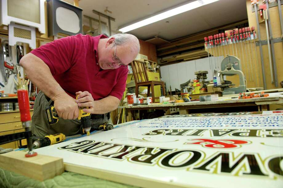 Bob Slesh, owner of Bob Slesh Woodworking & Repair, puts together a sign for his business in his workshop in Stamford, Conn., on Thursday, April 24, 2014. Photo: Lindsay Perry / Stamford Advocate