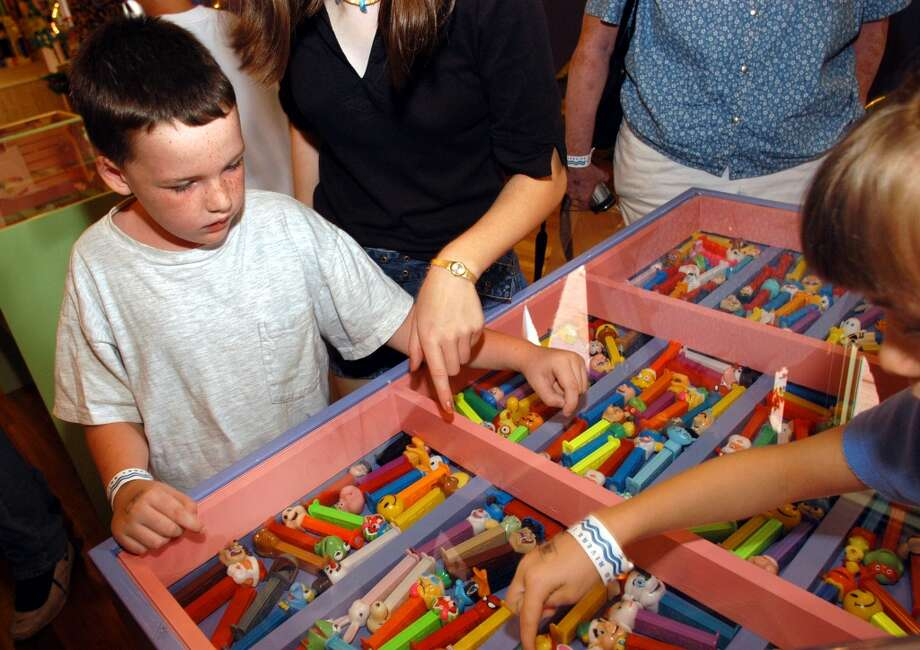 EASTON, PA - AUGUST 12:  Kyle Cowdrick (L) and his cousin Kalli Qutab, of Freehold, New Jersey pick one of the PEZ in the display case after reading a search challenge at the Easton Museum of PEZ Dispensers August 12, 2003 in Easton, Pennsylvania. The museum is set up to show how the PEZ dispenser designs reflect the time period in which they were made. The collection consists of about 1,500 PEZ dispensers from 1950 to present. (Photo by William Thomas Cain/Getty Images) Photo: Getty Images