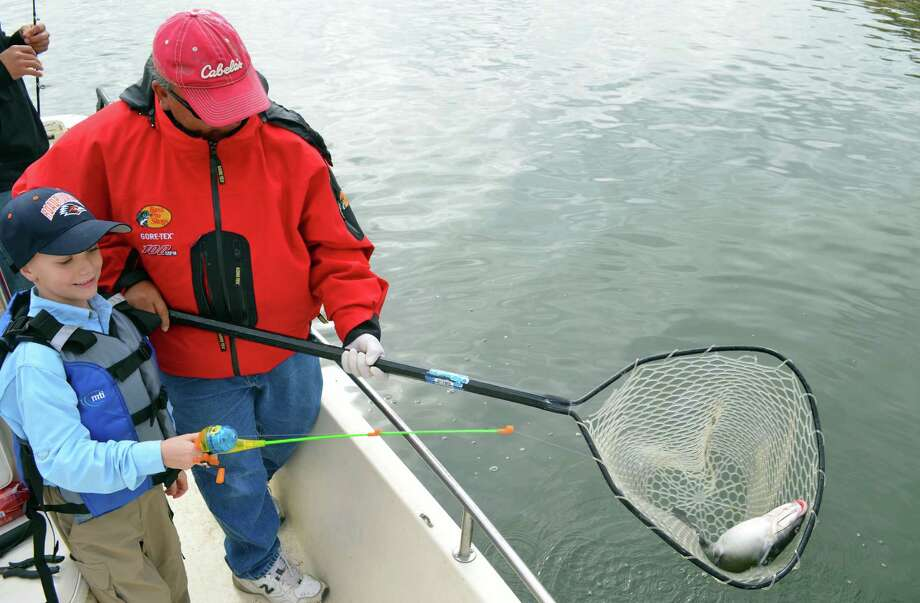 A nice channel catfish caught by Latham Koenen — while the youngster was practicing safe boating — is netted by veteran guide Manny Martinez during a trip on Calaveras Lake. Photo: Photos By Ralph Winingham / For The Express-News