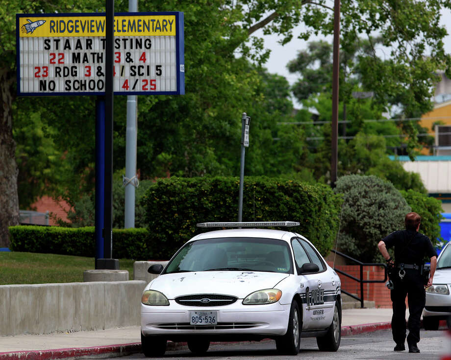 A law enforcement officer walks Thursday April 24, 2014 in the parking lot of Ridgeview Elementary School after a threat was made to an unnamed elementary school. School officials are taking extra precautions to ensure school safety. Photo: JOHN DAVENPORT, San Antonio Express-News / ©San Antonio Express-News/John Davenport