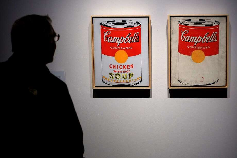"A man stands in front of a portrait of ""Campbell's Soup cans"" paintings by US artist Andy Warhol as part of the exhibition ""Warhol"" on April 17, 2014 in Rome. The works of the artist, father of American Pop Art, will be housed in the renovated rooms of the Museo della Fondazione Roma, Palazzo Cipolla from April 18 until September 28, 2014. The exhibition features over 150 works, paintings, photographs and sculptures from the collection of Warhol's friend Peter Brant. The works on display range from Warhol's early drawings right up to his Last Supper series, first presented in Milan in 1987 in what was to be his last exhibition before his death that same year. Photo: ALBERTO PIZZOLI, AFP/Getty Images"