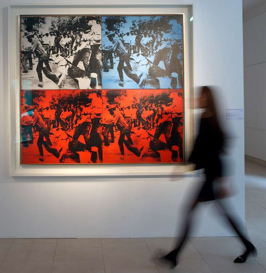 "A Christie's employee walks past ""Riot Race"" by Andy Warhol during a photo call in central London on April 11, 2014, ahead of an auction in New York. Photo: ANDREW COWIE, AFP/Getty Images"