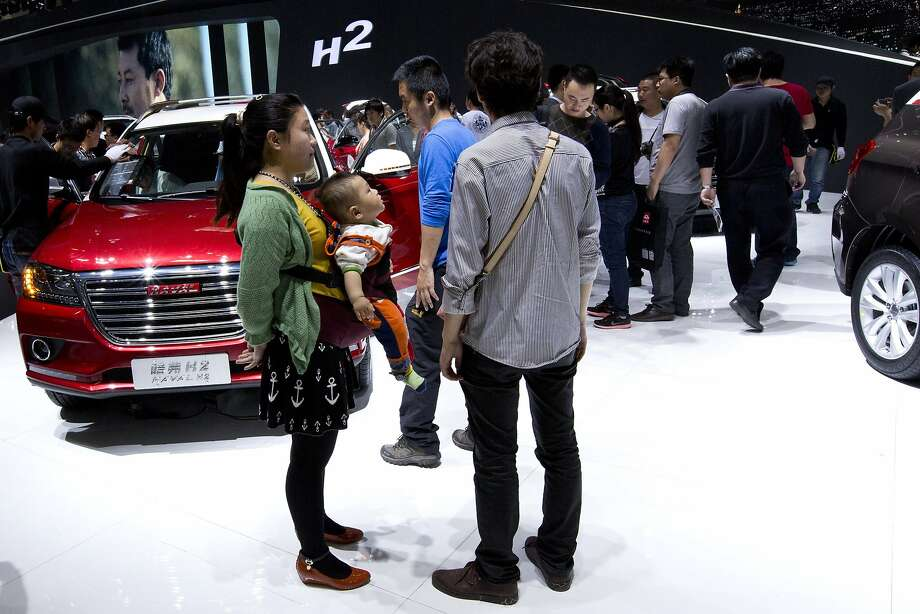 A family checks Chinese home-made Haval cars at the China Auto show in Beijing, Wednesday, April 23, 2014.  Photo: Alexander F. Yuan, Associated Press