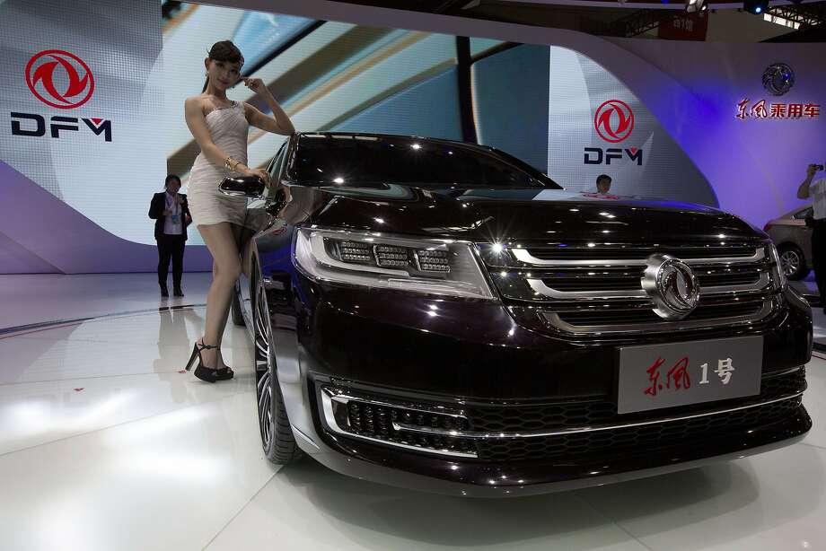 A model poses near Chinese carmaker Dong Feng Motors latest car displayed at the China Auto show held in Beijing, China, Sunday, April 20, 2014. Photo: Ng Han Guan, Associated Press