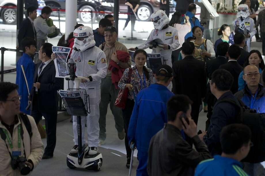 "Workers dressed like stormtroopers from the ""Star Wars"" movies distribute pamphlets at the China Auto show held in Beijing, China, Sunday, April 20, 2014.  Photo: Ng Han Guan, Associated Press"