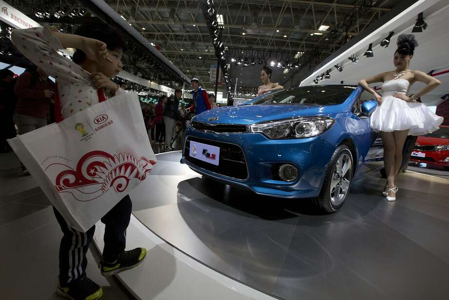 A young visitor walks near a car model posing next to a K3 sedan from Kia Motors displayed at the China Auto show in Beijing, China, Sunday, April 20, 2014. Photo: Ng Han Guan, Associated Press