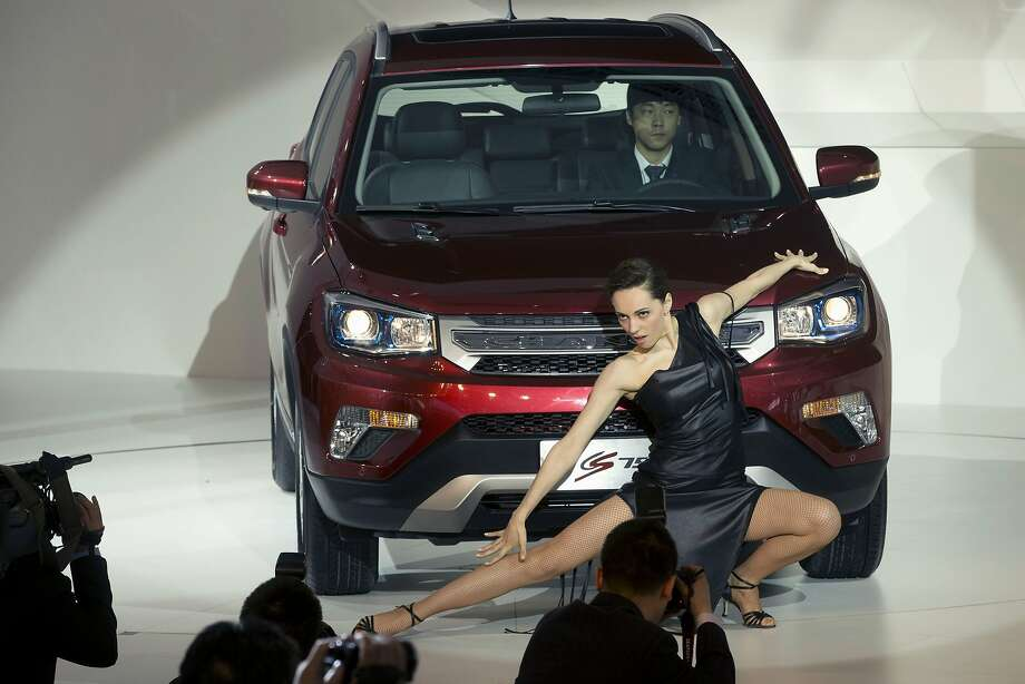 A dancer performs near the CS75 from Chinese car maker Changan at the China Auto show held in Beijing, China, Sunday, April 20, 2014. Photo: Ng Han Guan, Associated Press