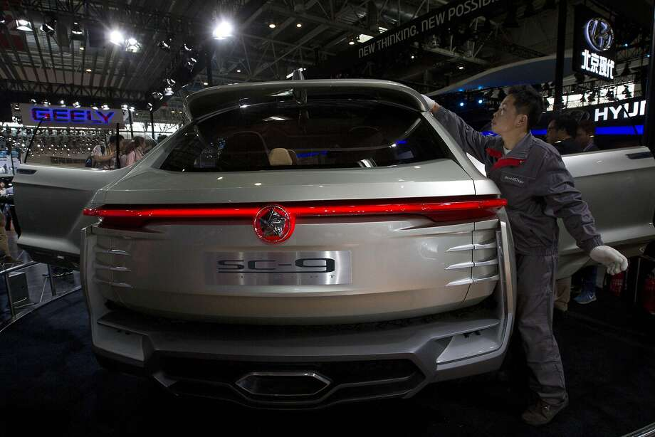 A worker cleans the top of the SC9 concept car from Chinese automaker JAC displayed at the China Auto show in Beijing, China, Sunday, April 20, 2014. Photo: Ng Han Guan, Associated Press